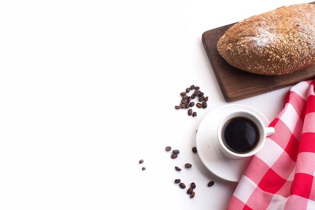 Schwarzer kaffee und vollkornbrot zum frühstück auf weißem hintergrund