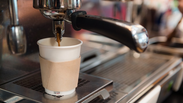 Schwarzer kaffeemorgen in pappbecher auf kaffeemaschine gestellt