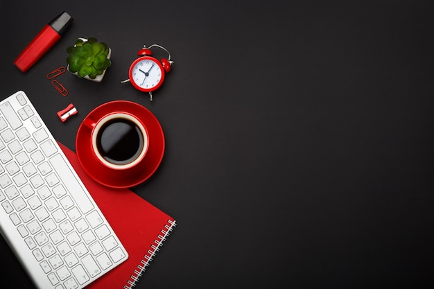 Schwarzer kaffeetasse-notizblockwecker-blumentastatur-leerstellendesktop des hintergrundes roter