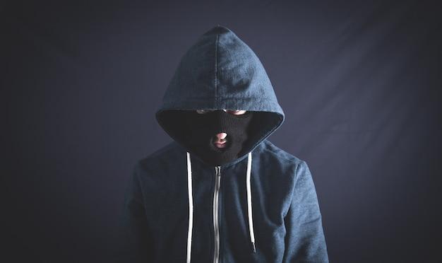 Schwarzer kapuzenpulli des mannes mit skimaske, die auf einem dunklen hintergrund steht.