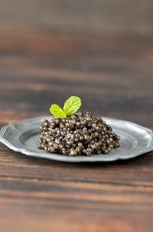 Schwarzer kaviar auf silberner vintage-platten-nahaufnahme