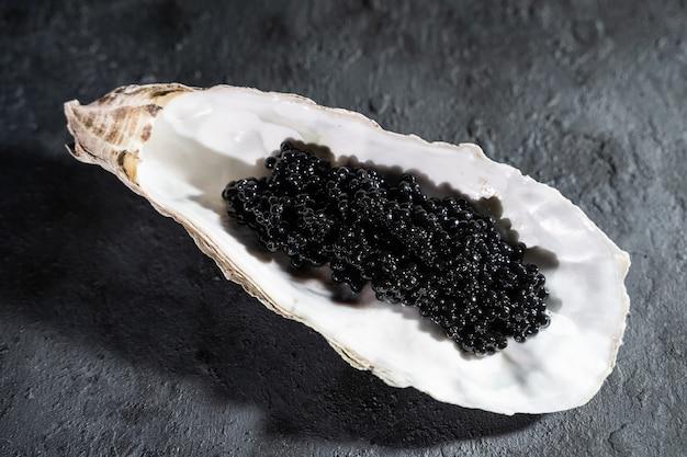 Schwarzer kaviar in der austernschale auf schwarzem schieferhintergrund