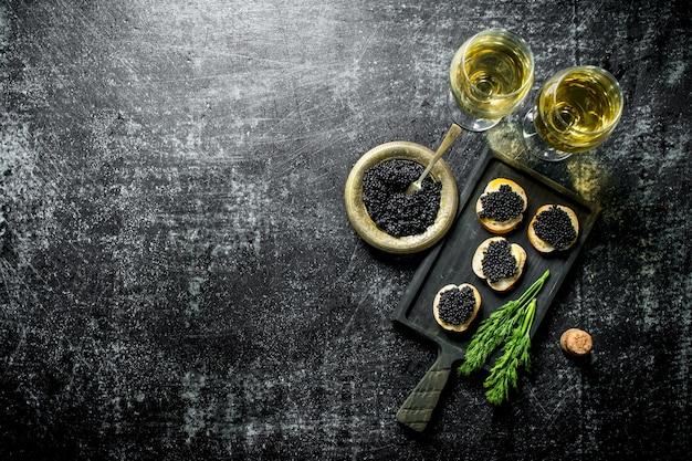 Schwarzer kaviar in einer schüssel und sandwiches mit kaviar auf einem schneidebrett mit dill und weißwein. auf schwarzer rustikaler oberfläche