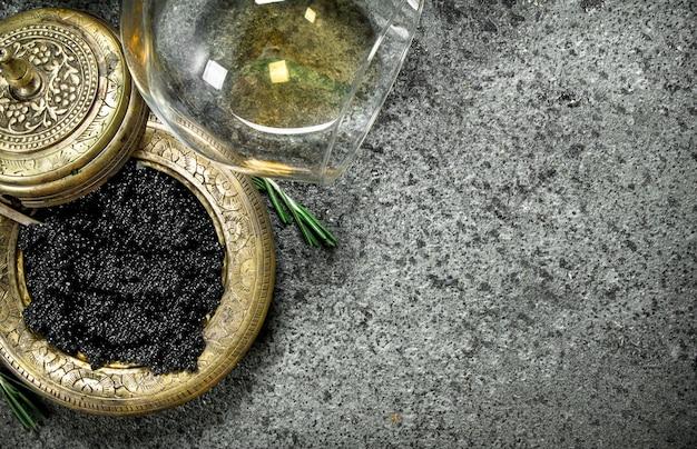 Schwarzer kaviar mit einem glas weißwein. auf rustikalem hintergrund.