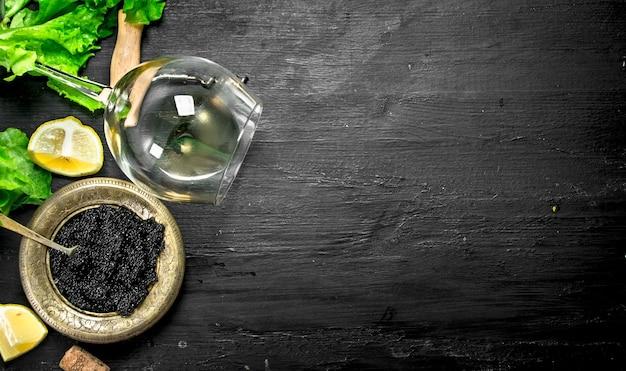 Schwarzer kaviar mit weißwein und kräutern. auf einer schwarzen tafel.