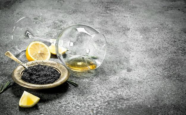 Schwarzer kaviar mit weißwein und zitrone. auf rustikalem hintergrund.
