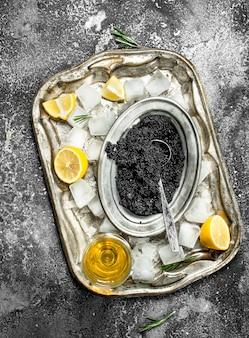 Schwarzer kaviar mit weißwein und zitronenscheiben. auf rustikalem hintergrund.