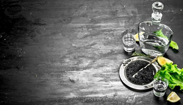 Schwarzer kaviar mit wodka und zitronenscheiben. auf einer schwarzen tafel.