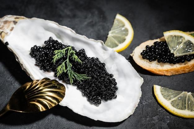 Schwarzer kaviar mit zitronenscheiben auf einem schwarzen holztisch. der goldene löffel liegt in der nähe. köstliche köstlichkeiten. reichhaltiges essen. nahansicht.