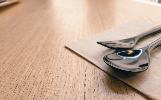 Schwarzer keramischer löffel und gabel auf copyspace holztisch im restauranthintergrund.