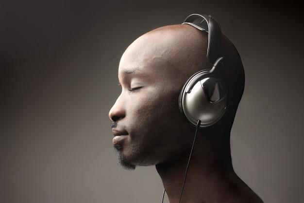 Schwarzer kerl auf hörender musik des profils mit kopfhörern