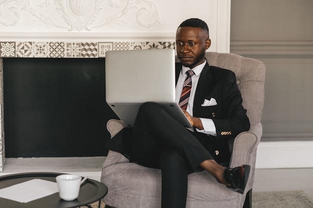 Schwarzer kerl in einem schwarzen anzug, der in einem stuhl mit einem laptop sitzt. hochwertiges foto