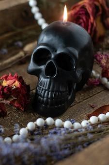 Schwarzer kerzenschädel auf hexentisch. okkultes, esoterisches, wahrsagerei und wicca-konzept. halloween-konzept