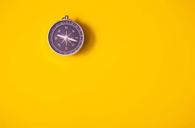 Schwarzer kompass auf gelbem hintergrund, ausrüstung für die reise, tourismus und geschäft, draufsicht