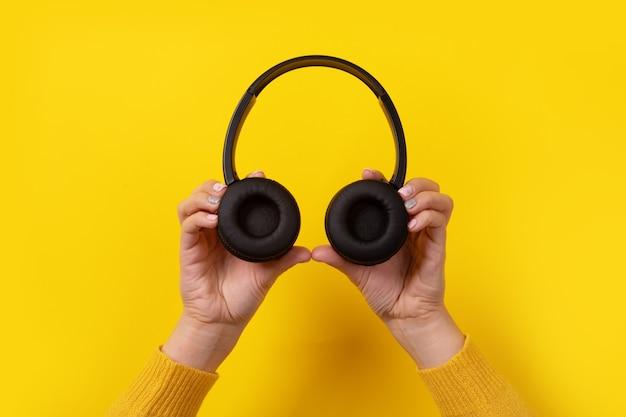 Schwarzer kopfhörer in der hand auf gelb