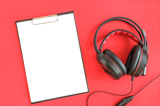 Schwarzer kopfhörer und zwischenablage mit weißem blankopapier