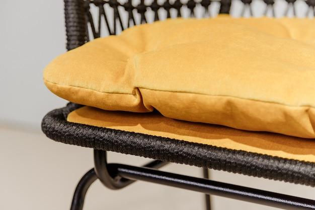 Schwarzer korbstuhl mit gelben kissendetails