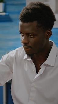 Schwarzer künstler mit bleistift und weißer leinwand auf staffelei für den design- und zeichenprozess im werkstattraum. afroamerikaner, der ein wunderschönes meisterwerk für das kunstkonzept schafft