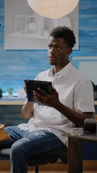 Schwarzer künstler mit digitalem tablet im werkstattstudio