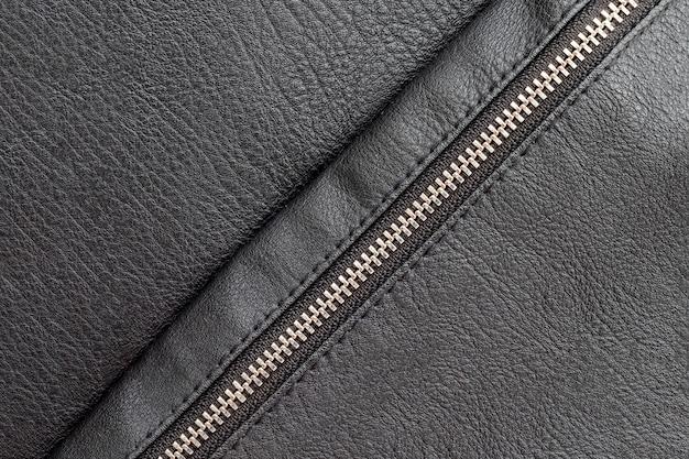 Schwarzer kunstlederhintergrund mit geschlossenem diagonalem reißverschluss