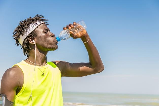 Schwarzer läufer, der trinkendes energiegetränk der pause am strand am sommer macht