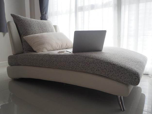 Schwarzer laptop auf weißer moderner couch mit weißem vorhangbeschaffenheitshintergrund.