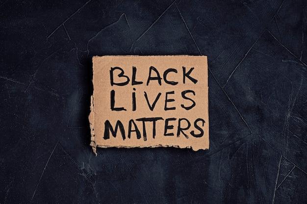 Schwarzer leben materietext auf pappe über dunklem hintergrund