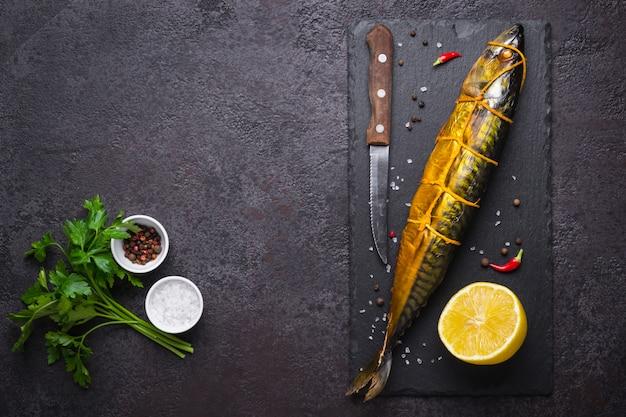 Schwarzer lebensmittelhintergrund mit geräucherten makrelenfischen und -gewürzen