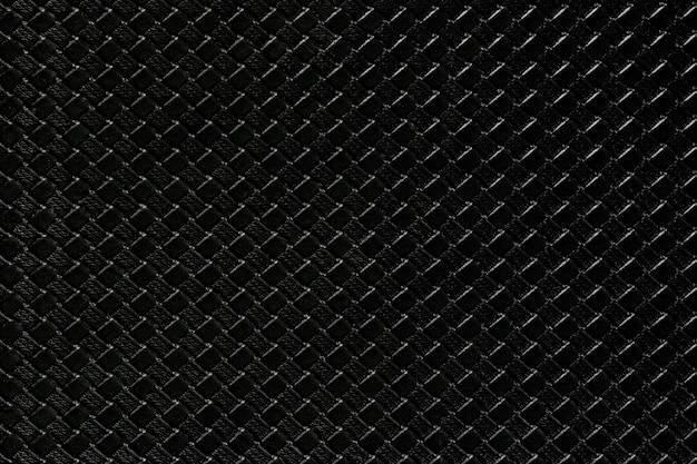 Schwarzer lederner hintergrund mit nachgemachter webartbeschaffenheit. glänzende kunstlederstruktur.