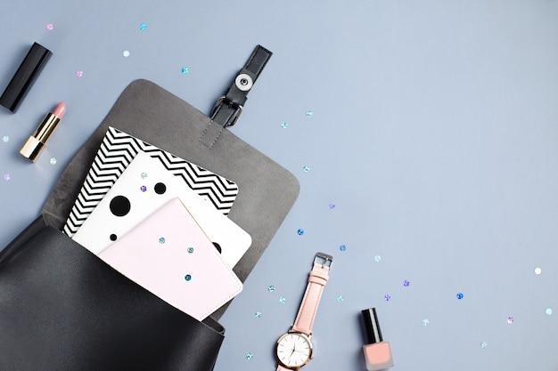 Schwarzer lederrucksack, schreibwaren und notizbücher auf grau