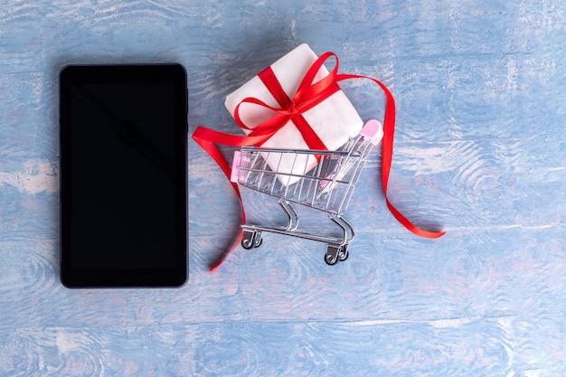 Schwarzer leerer tablett- oder handybildschirm und wagen mit geschenkbox auf blauem hölzernem hintergrund, kopienraum. online-glückwunschkonzept. online-shopping-konzept