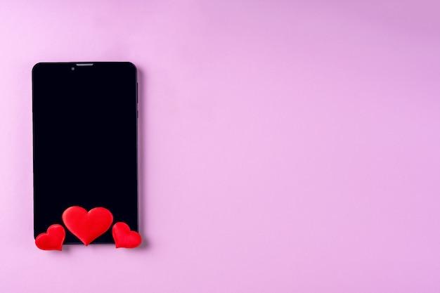 Schwarzer leerer telefonbildschirm mit roter herzform auf rosa hintergrund, kopienraum, minimalismus, flache lage. valentinstag konzept. konzept, um in sozialen netzwerken oder dating-app zu mögen