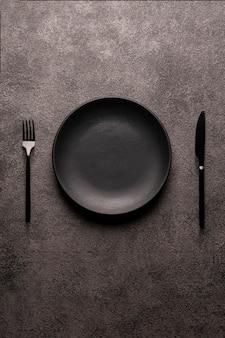 Schwarzer leerer teller und besteck, gabel und messer auf einem dunklen strukturierten hintergrund. das konzept eines layouts für die gestaltung eines restaurantmenüs, einer website oder eines designs. vertikales layout von lebensmittelfotos.