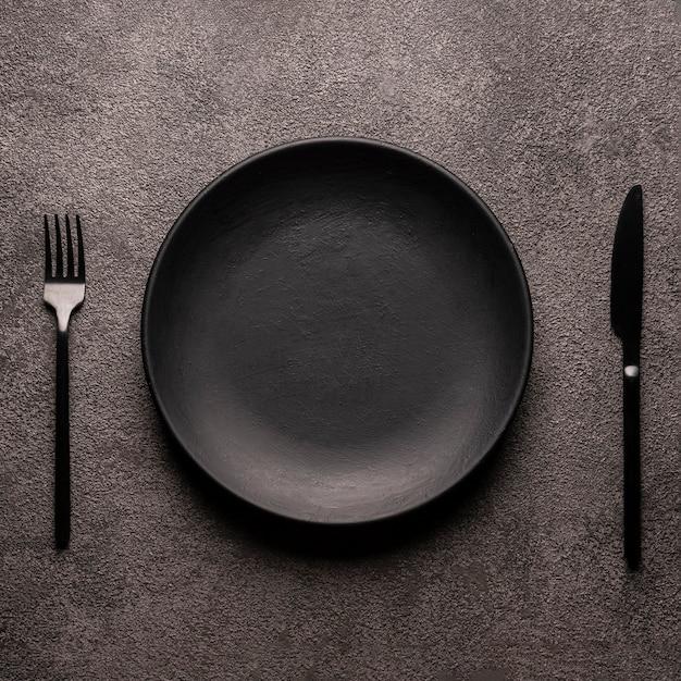 Schwarzer leerer teller und besteck, gabel und messer auf einem dunklen strukturierten tisch. konzept für die gestaltung eines restaurantmenüs, einer website oder eines designs. quadratisches layout