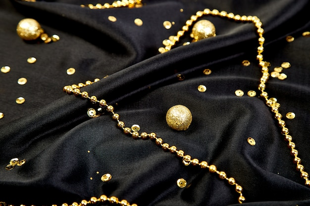 Schwarzer luxushintergrund mit goldglänzenden bällen.