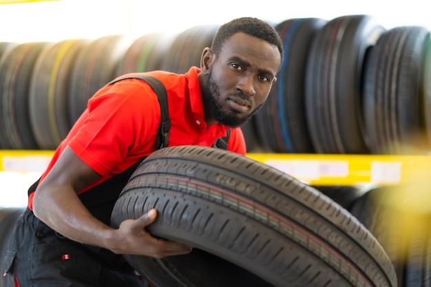 Schwarzer männlicher mechaniker, der einen reifen hält und radreifen im autoreparaturservice und im autogeschäft zeigt. sachkundiger mechaniker, der in einer autowerkstatt arbeitet.