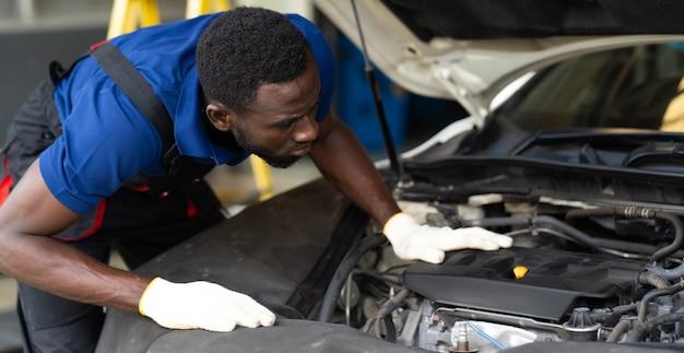 Schwarzer männlicher mechaniker repariert auto in garage. autowartungs- und autowerkstattkonzept.