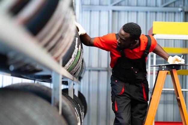 Schwarzer männlicher mechaniker wählt autoreifen in einem reifengeschäft. sachkundiger mechaniker, der in einer autowerkstatt arbeitet.