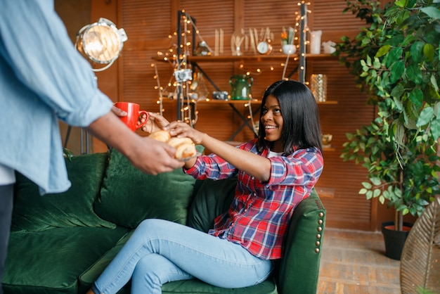 Schwarzer mann bringt kaffee und bäckerei zu seiner frau, romantisches frühstück zu hause.