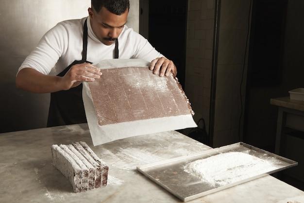 Schwarzer mann chef, der frisch gebackenen schokoladenkuchen für verpackung, handwerkliches kochverfahren in süßwaren vorbereitet