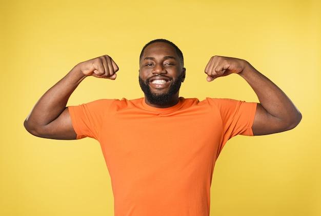 Schwarzer mann denkt, starke muskeln zu haben. gelbe wand