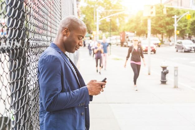 Schwarzer mann, der am telefon in new york schreibt