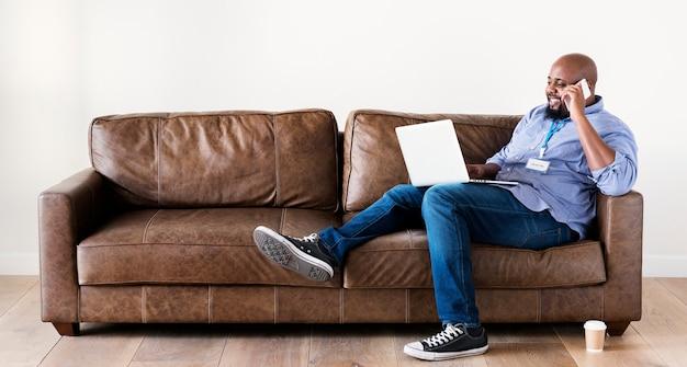 Schwarzer mann, der an laptop arbeitet