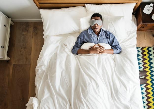 Schwarzer mann, der auf bett mit augenmaske schläft