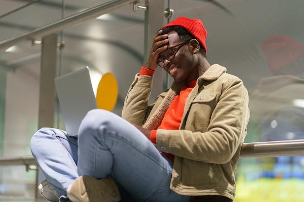 Schwarzer mann, der auf dem boden sitzt und im video-chat auf laptop spricht, der in den sozialen netzwerken unterhält und lächelt