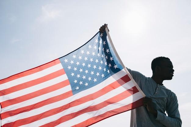 Schwarzer mann, der breite wellenartig bewegende amerikanische flagge hält