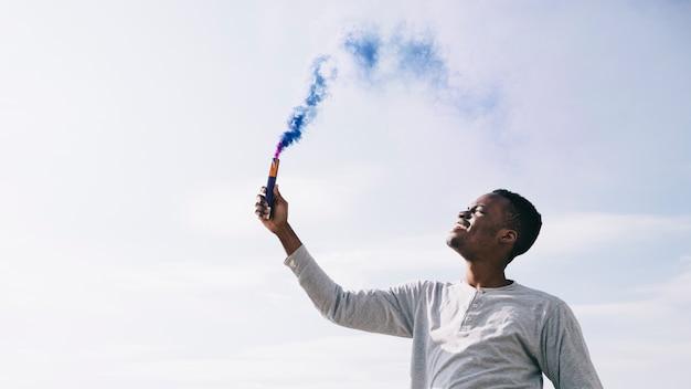 Schwarzer mann, der dunkelblaue rauchbomben hält