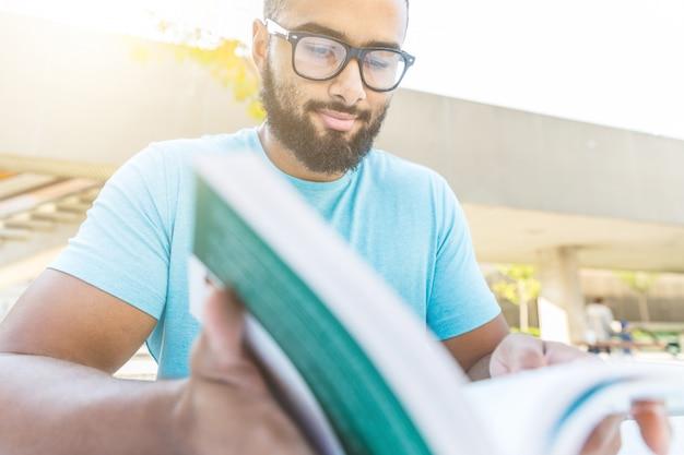 Schwarzer mann, der ein buch in der stadt liest