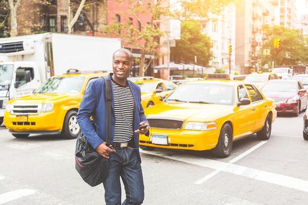 Schwarzer mann, der eine straße in new york kreuzt.