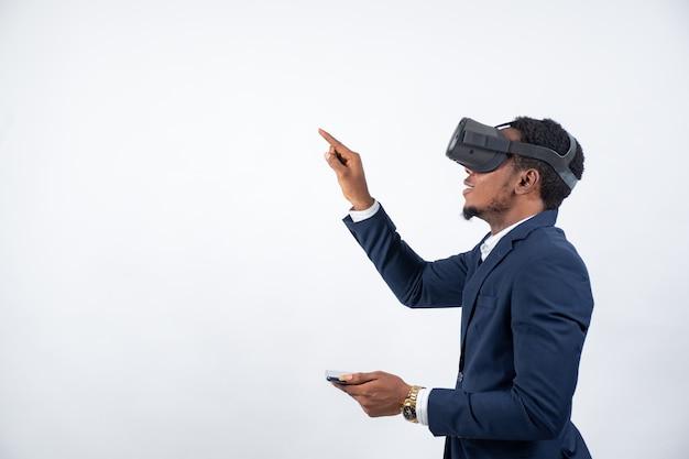 Schwarzer mann, der einen anzug trägt und ein virtual-reality-headset und ein telefon verwendet